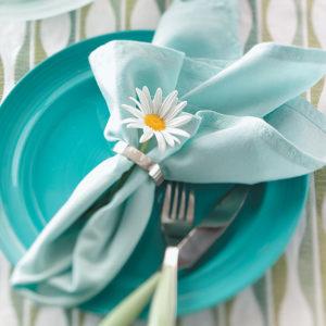 Insert the stem of a fresh flower through the napkin ring.
